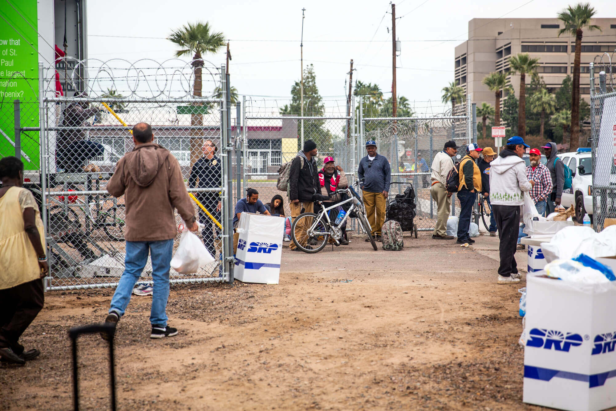People gaather in an empty lot converted into a giving station near the Human Services Campus in downtown Phoenix on Thursday, Nov. 22, 2018. Those who don't get access to the shelter on the campus often camp out and congregate in nearby areas.